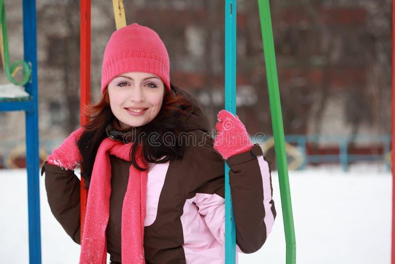 Femme dans le chapeau rose se reposant sur l'oscillation en hiver image libre de droits