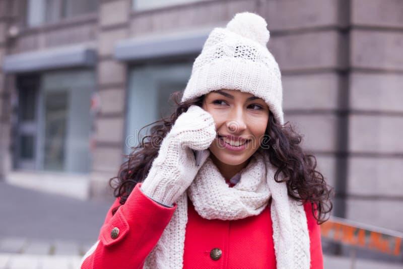 Femme dans le chapeau rouge de manteau et de laine et gants avec le smartphone en Han photo stock