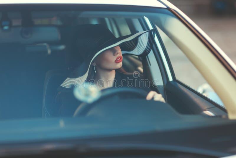 Femme dans le chapeau se reposant derrière la roue d'une voiture images libres de droits