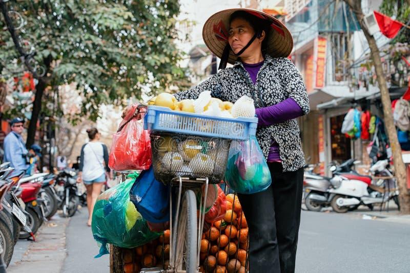 Femme dans le chapeau traditionnel vendant le fruit de la bicyclette images stock