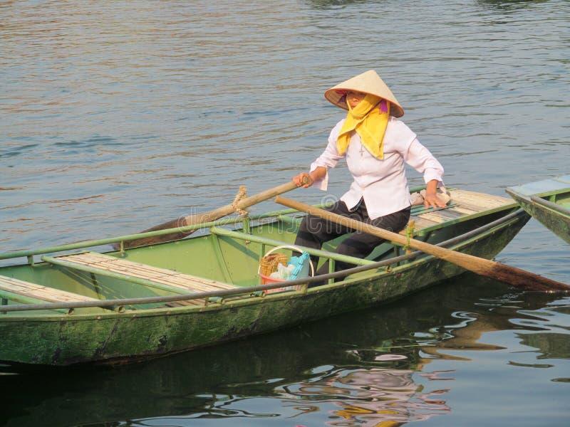 Femme dans le chapeau triangulaire dans un bateau de palette au Vietnam photo stock