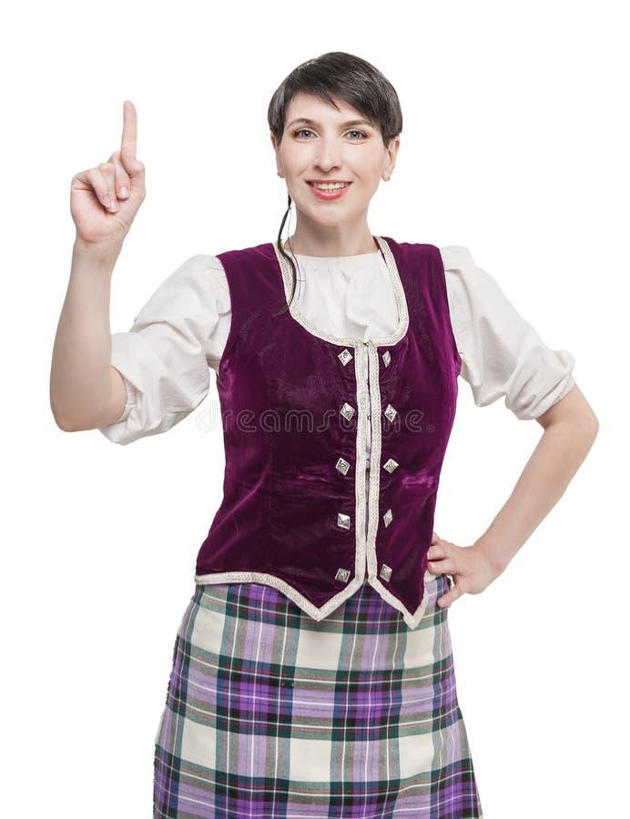 Femme dans le costume écossais traditionnel montrant sur quelque chose photographie stock