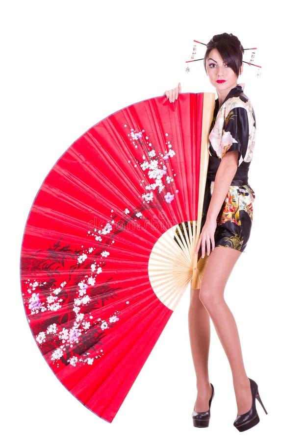 Femme dans le costume asiatique avec le ventilateur asiatique rouge photos stock