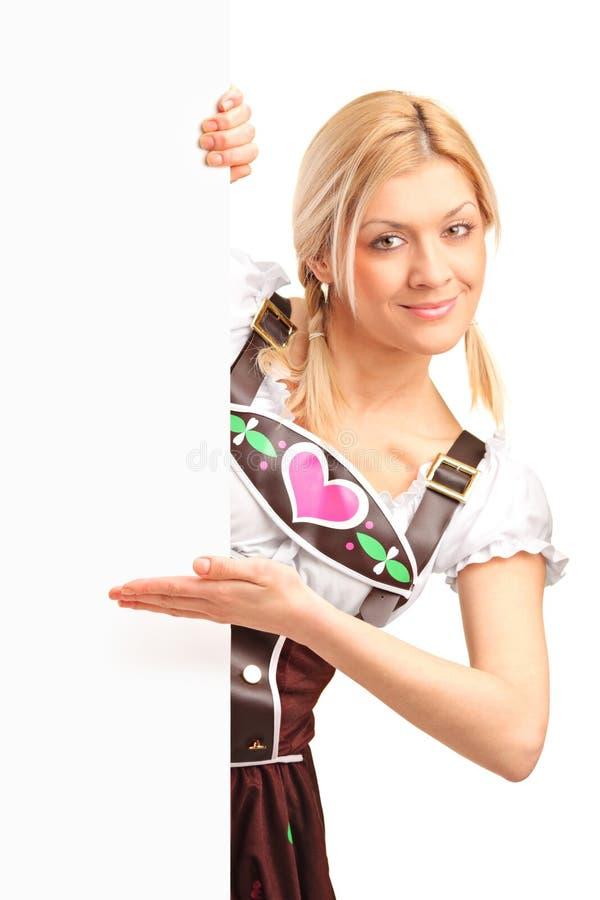 Femme dans le costume bavarois retenant un panneau images stock
