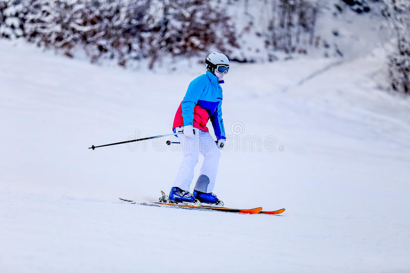 Femme dans le costume de ski blanc sur la pente de montagne photographie stock libre de droits