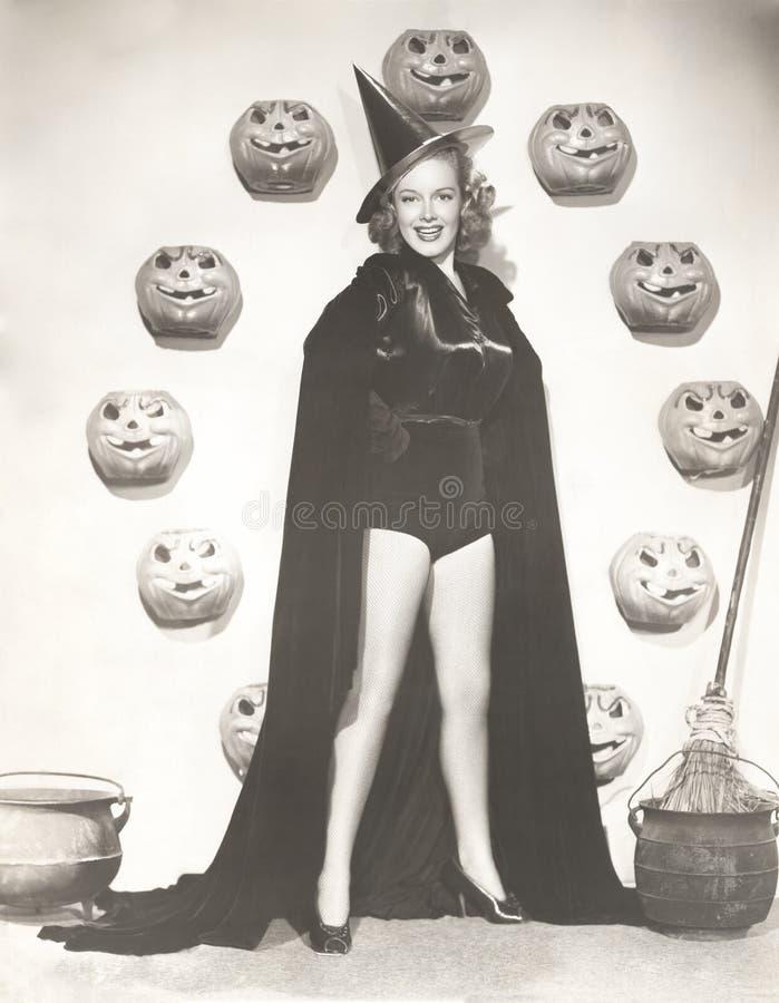 Femme dans le costume de sorcière entouré par les potirons découpés photos libres de droits