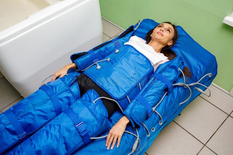 Femme dans le costume pressotherapy se trouvant vers le bas ayant la thérapie de pression image stock