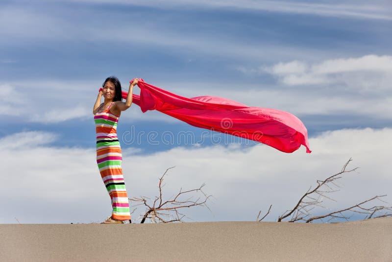 Femme dans le désert avec le tissu rose. photo stock