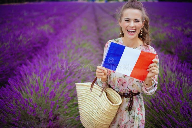 Femme dans le domaine de lavande avec le sac de paille montrant le drapeau français photographie stock