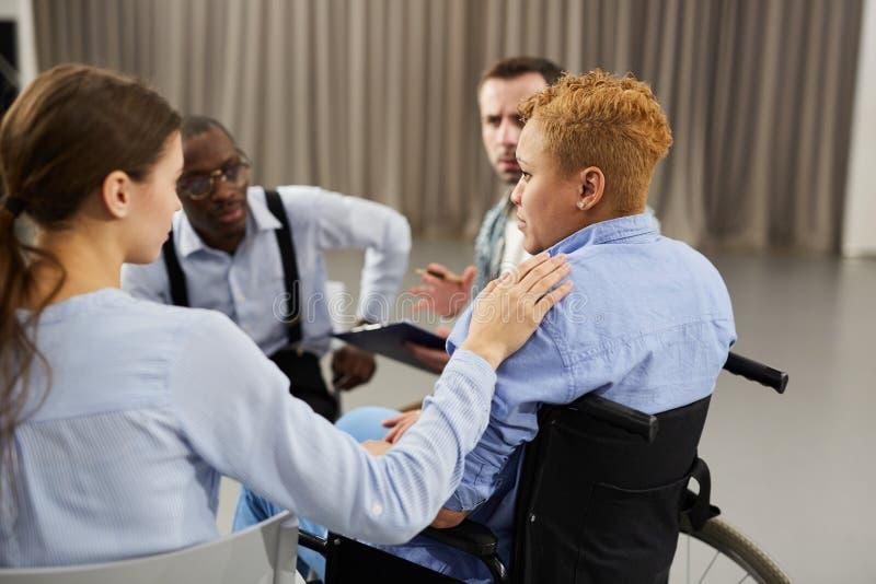 Femme dans le fauteuil roulant assistant à la réunion de soutien images stock