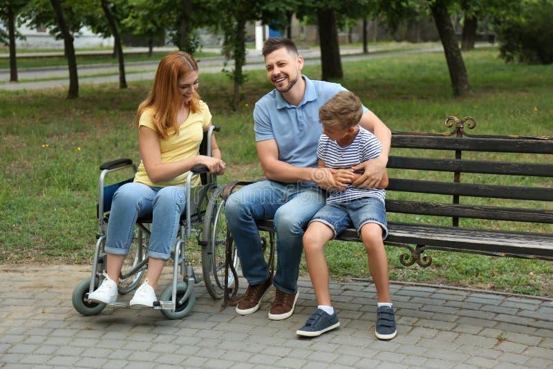 Femme dans le fauteuil roulant avec sa famille image libre de droits