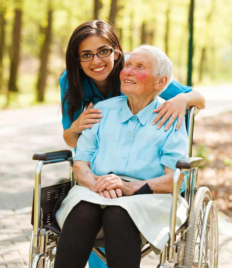 Femme dans le fauteuil roulant et une infirmière photos stock