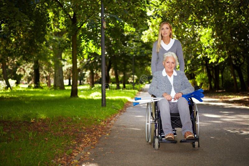 Femme dans le fauteuil roulant pilotant en stationnement photographie stock