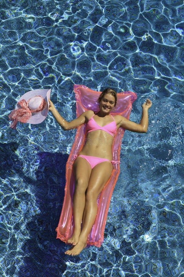 Femme dans le flottement rose de bikini photos stock
