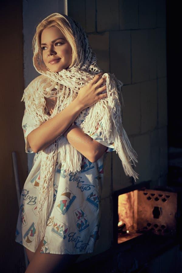 Femme dans le foulard se dorant près du fourneau de chauffage photographie stock