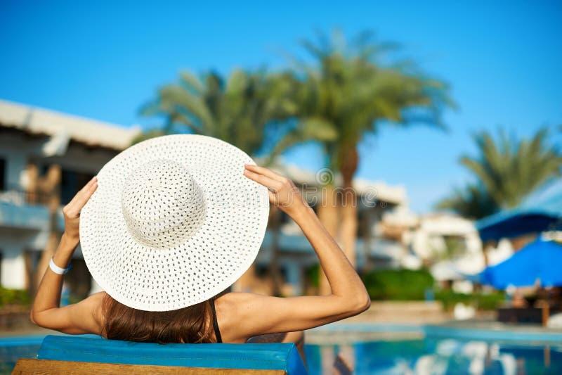 Femme dans le grand chapeau blanc se trouvant sur un canapé près de la piscine à l'hôtel, heure d'été de concept de voyager images libres de droits