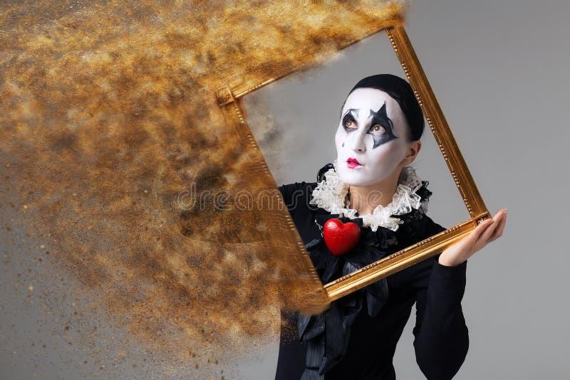 Femme dans le harlequin de déguisement dans le cadre de tableau photos libres de droits