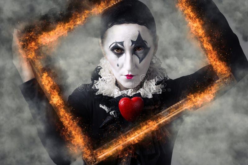 Femme dans le harlequin de déguisement dans le cadre de tableau images stock