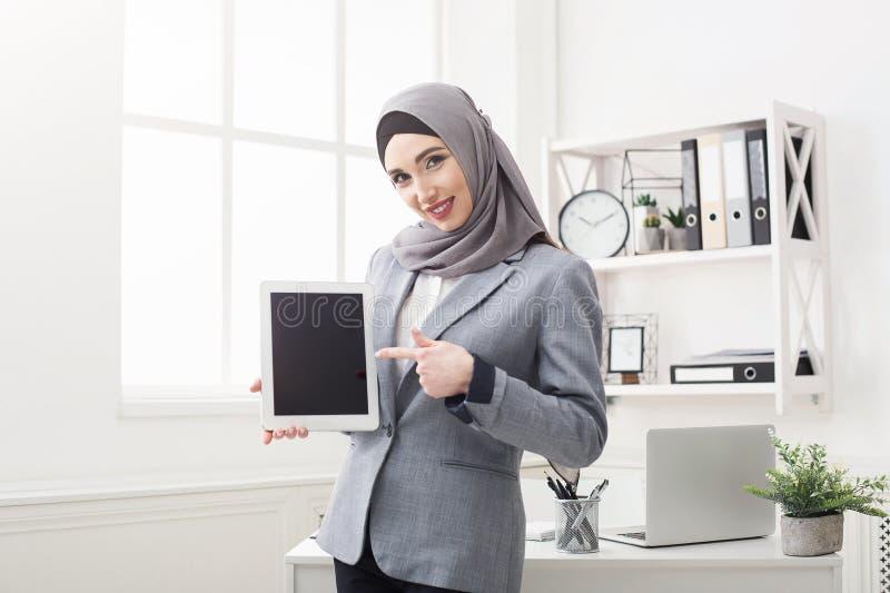 Femme dans le hijab tenant le comprimé avec l'écran vide photographie stock libre de droits