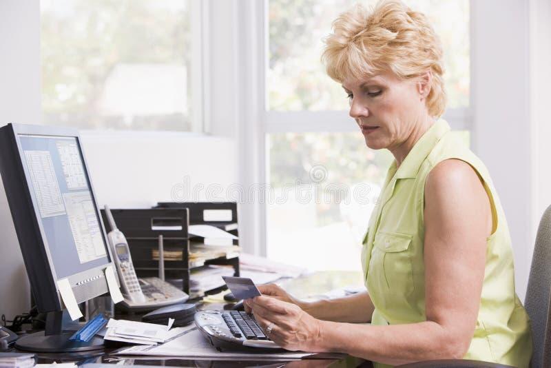 Femme dans le Home Office à l'ordinateur photographie stock libre de droits