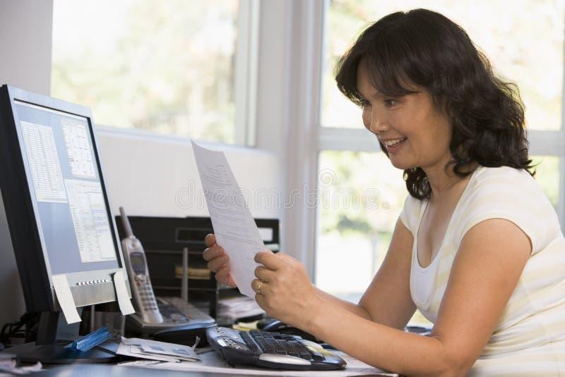 Femme dans le Home Office avec l'ordinateur et les écritures photographie stock