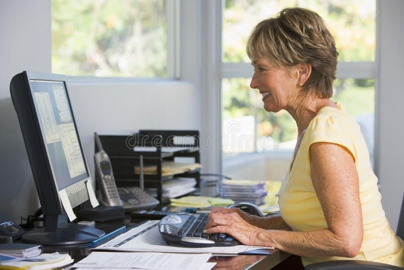 Femme dans le Home Office utilisant le sourire d'ordinateur images stock