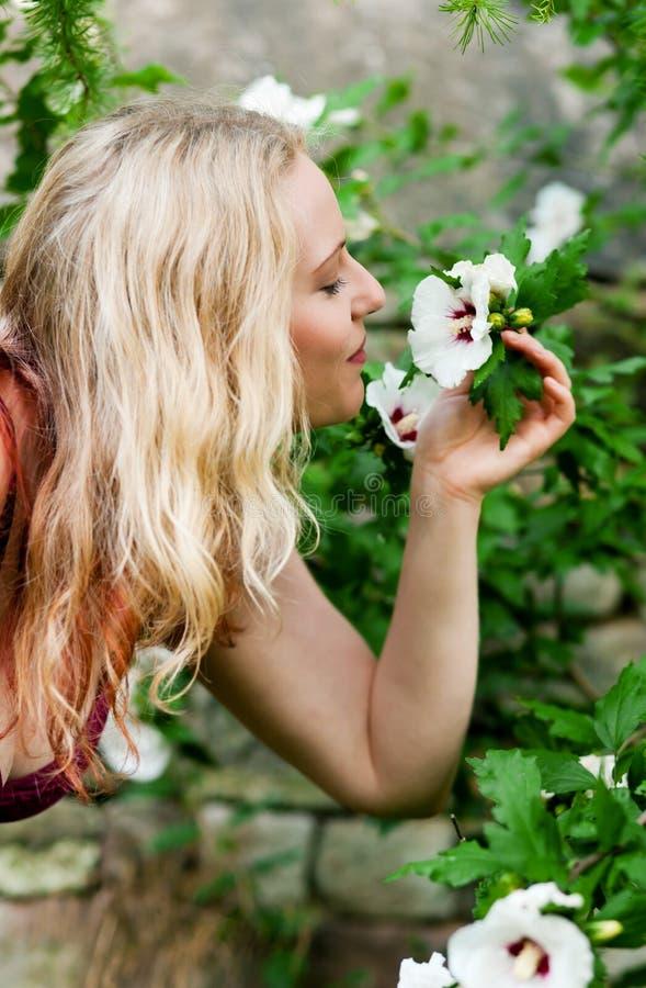 Femme dans le jardin reniflant aux fleurs photos libres de droits