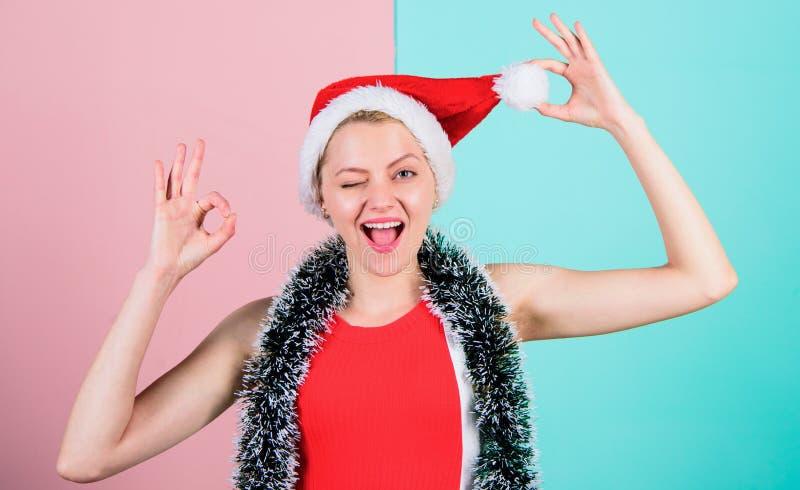 Femme dans le jeu de chapeau de Santa de Noël avec le rose de pompon et le fond bleu Concept d'attribut de Noël Visage gai de fil photo stock