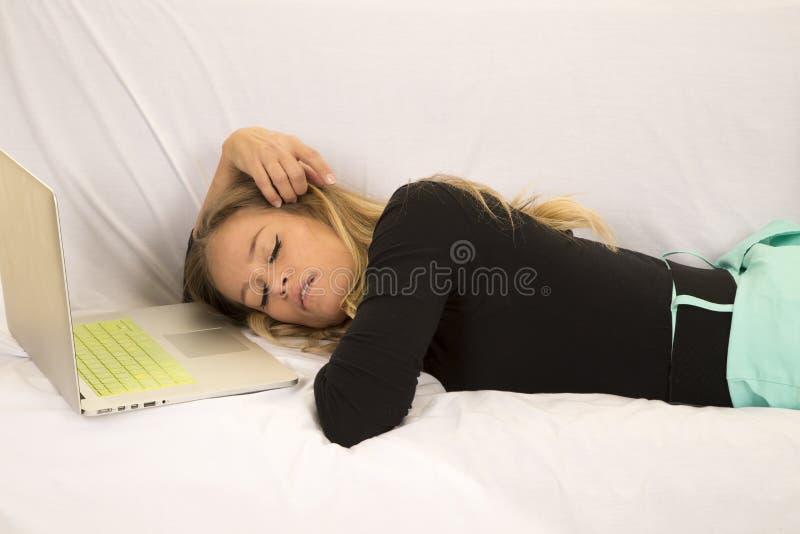 Femme dans le layign vert de jupe avec le sommeil d'ordinateur portable photographie stock