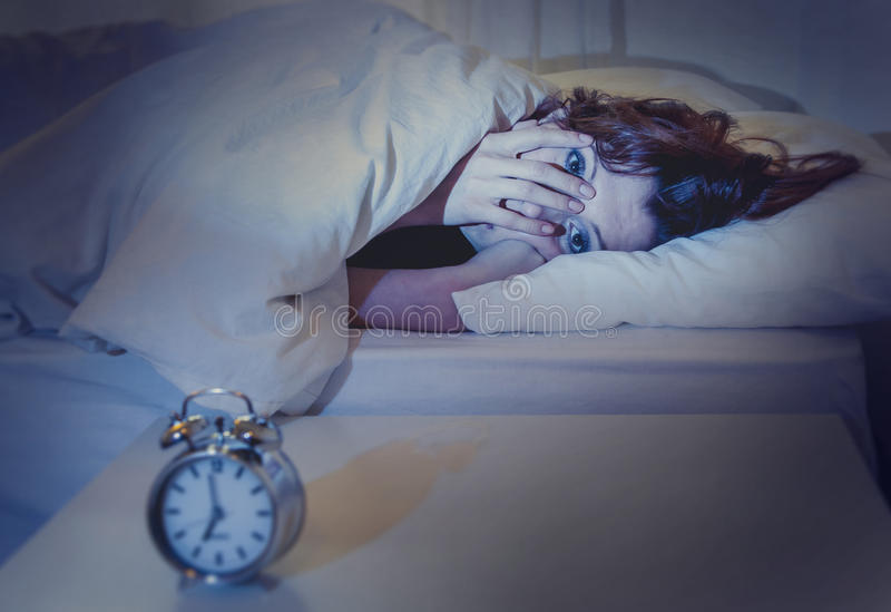 Femme dans le lit avec l'insomnie qui ne peut pas dormir le fond blanc photographie stock