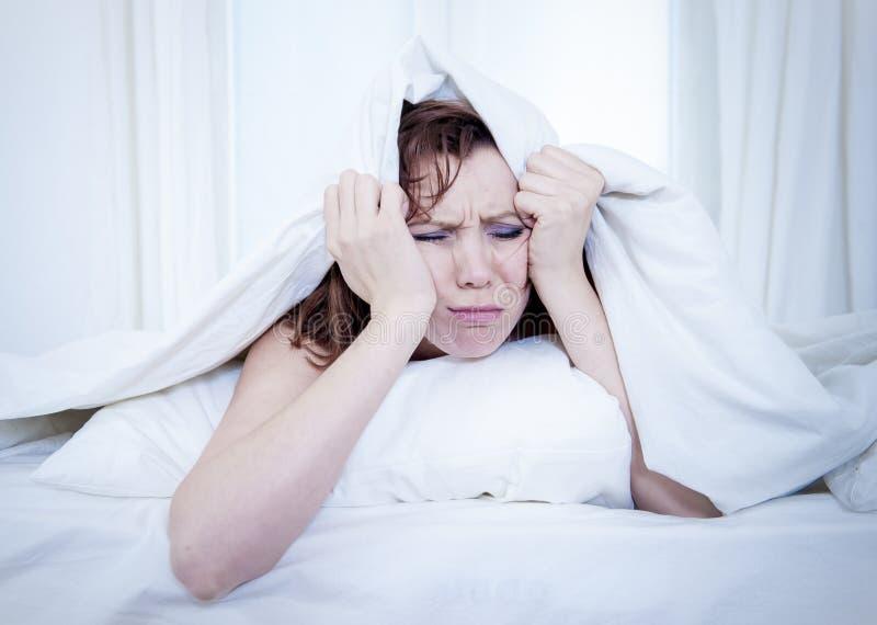 Femme dans le lit avec l'insomnie qui ne peut pas dormir le fond blanc images libres de droits
