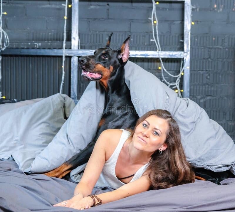 Femme dans le lit avec le grand chien photo stock