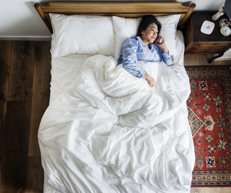 Femme dans le lit parlant au téléphone photo stock