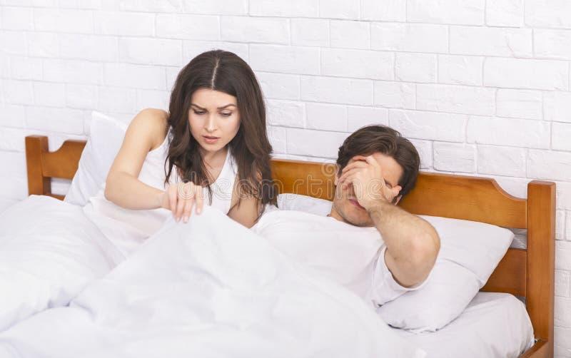 Femme dans le lit regardant sous la couverture, homme avec le dysfonctionnement ?rectile photographie stock libre de droits
