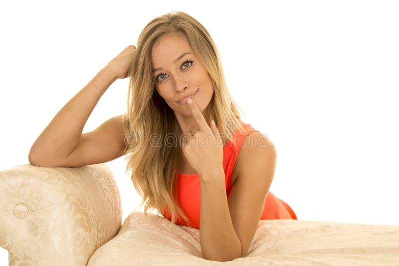 Femme dans le maigre de rouge sur le doigt de sofa de vive voix photographie stock