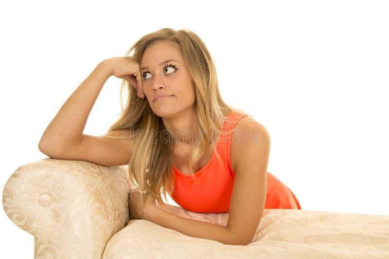 Femme dans le maigre de rouge sur le regard de sofa au côté photographie stock libre de droits