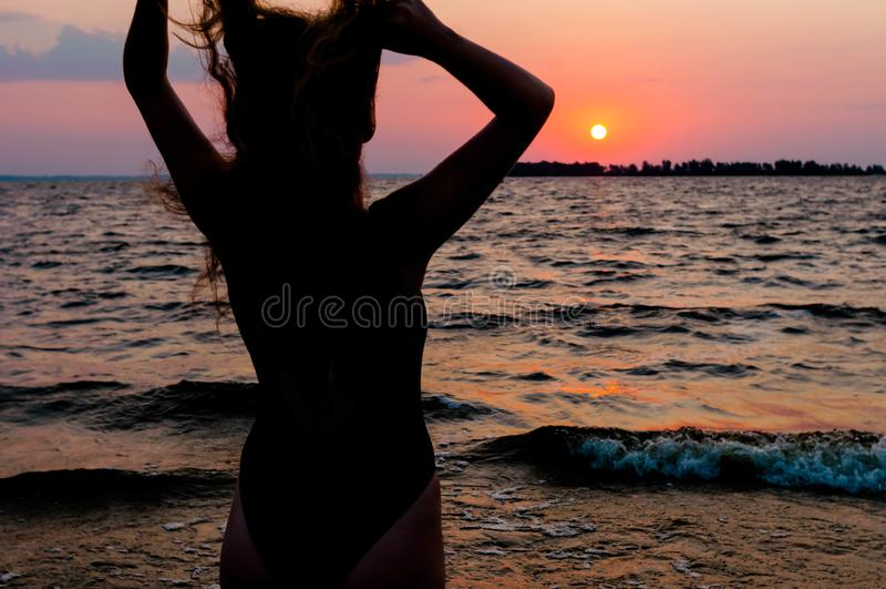 Femme dans le maillot de bain avec les bras augmentés corrigeant des cheveux et regardant le lever de soleil stupéfiant photos libres de droits