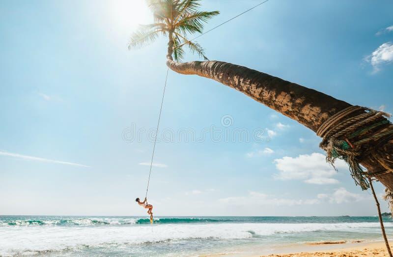 Femme dans le maillot de bain blanc balançant sur l'oscillation tropicale de paume au-dessus des ressacs Vacances tropicales de p photographie stock libre de droits