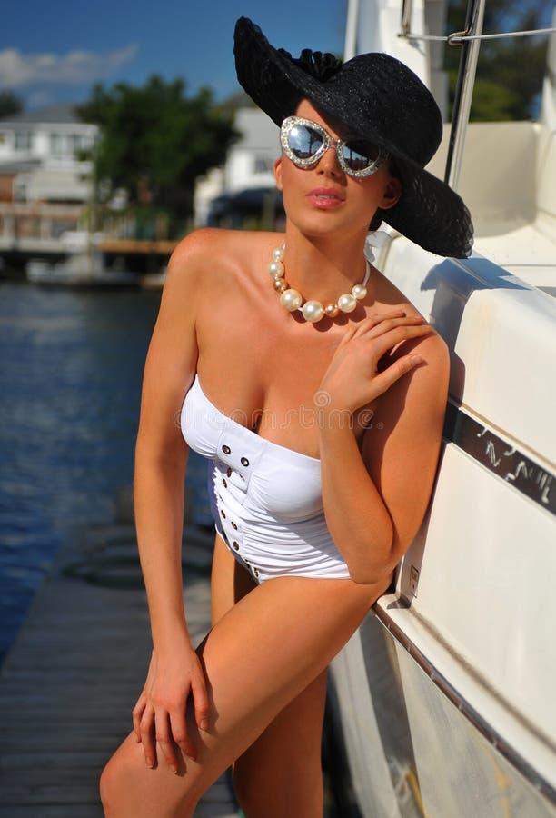 Femme dans le maillot de bain, le chapeau blanc et des lunettes de soleil posant assez au yacht de luxe photographie stock libre de droits
