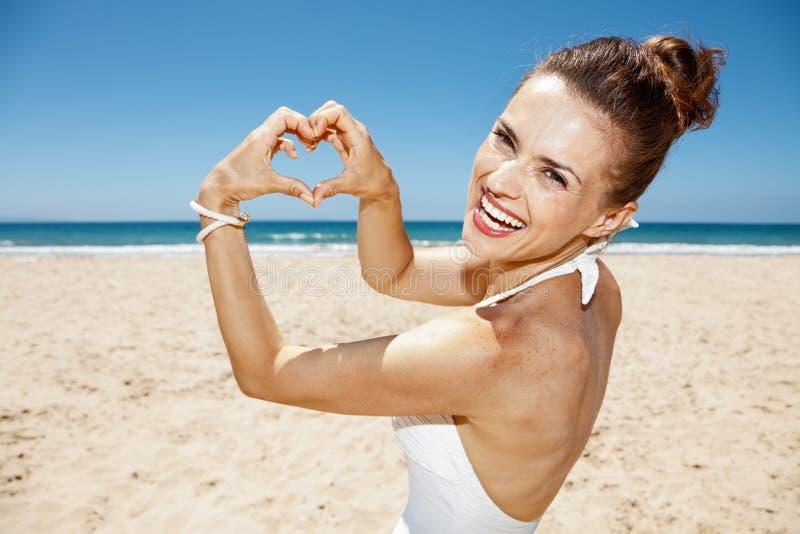 Femme dans le maillot de bain montrant les mains en forme de coeur à la plage sablonneuse photo stock