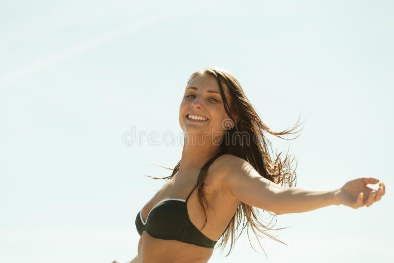 Femme dans le maillot de bain noir de bikini ayant l'amusement dehors images stock