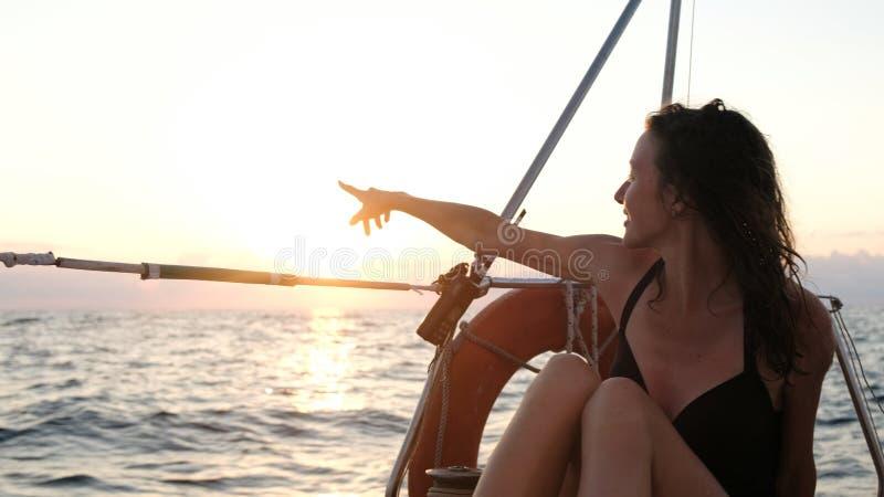 Femme dans le maillot de bain sur une navigation de yacht en mer et montrer son doigt au coucher du soleil images libres de droits