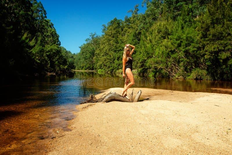 Femme dans le maillot de bain tanding sur la barre de sable noueuse d'ouverture photos stock