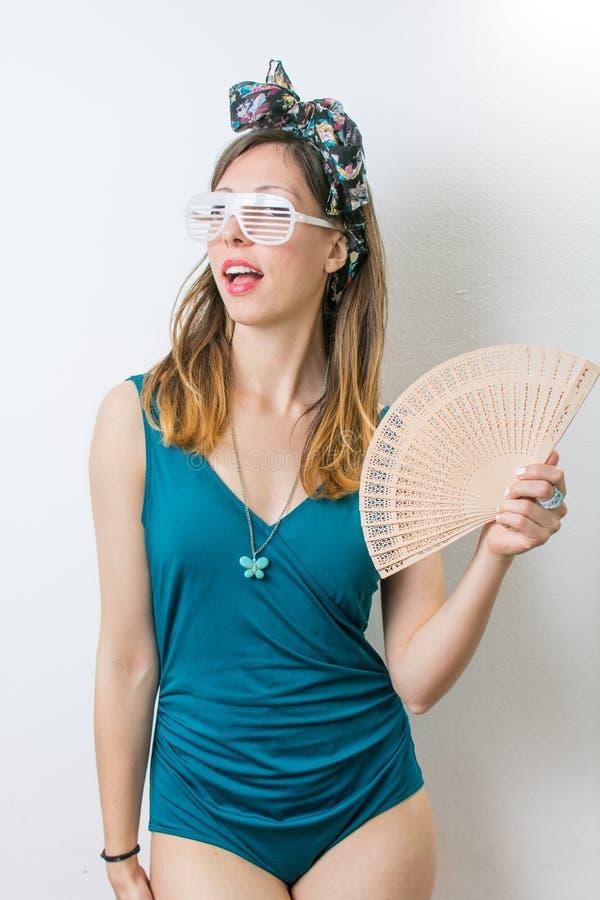 Femme dans le maillot de bain tenant la fan de main images stock