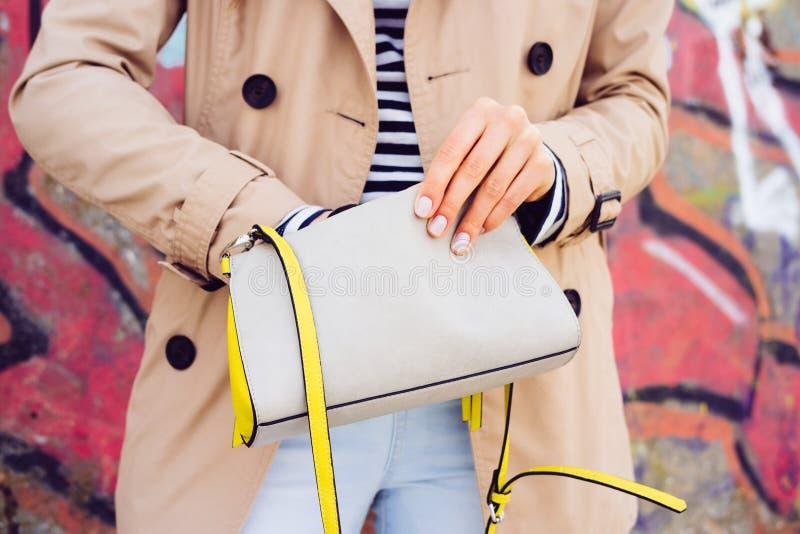 Femme dans le manteau beige et des jeans tenant le sac à main d'une dame sur un dos image stock