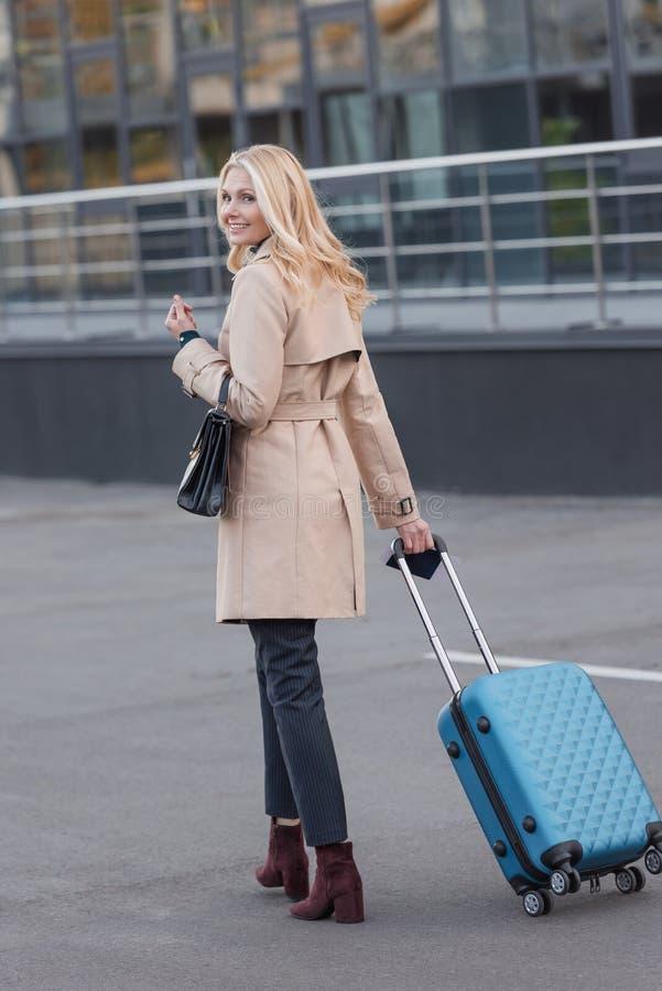 Femme dans le manteau de fossé avec le bagage photo stock