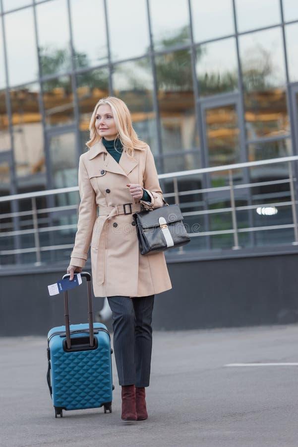 Femme dans le manteau de fossé avec le bagage photos libres de droits