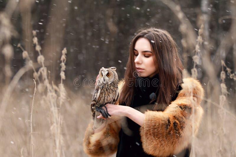 Femme dans le manteau de fourrure avec le hibou en main par la première neige d'automne Beautif image stock