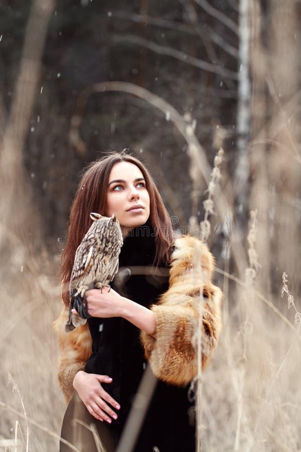 Femme dans le manteau de fourrure avec le hibou en main par la première neige d'automne Beautif photographie stock libre de droits