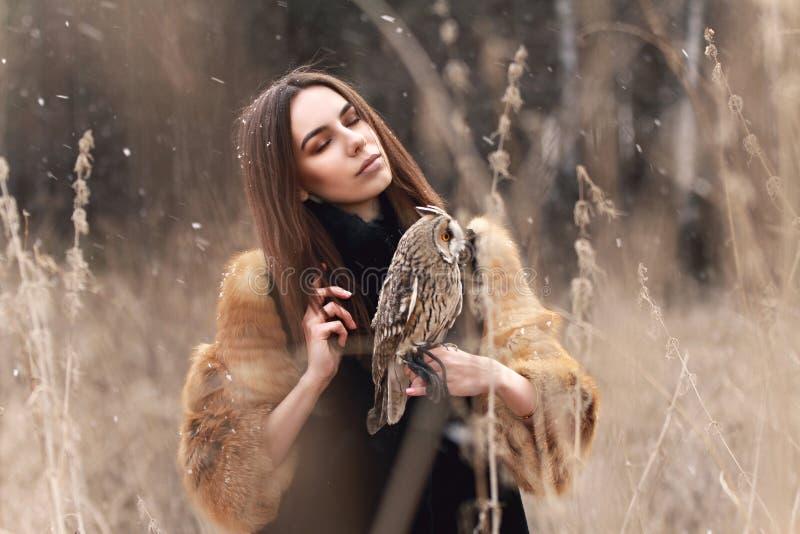 Femme dans le manteau de fourrure avec le hibou en main par la première neige d'automne Beautif image libre de droits